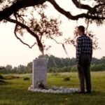 Forrest stands at Jenny's grave under the tree where she was buried