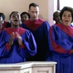 Forrest sings along with the all-black gospel choir