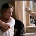 Jenny sits quietly in her room thinking with the flowers that Forrest picked